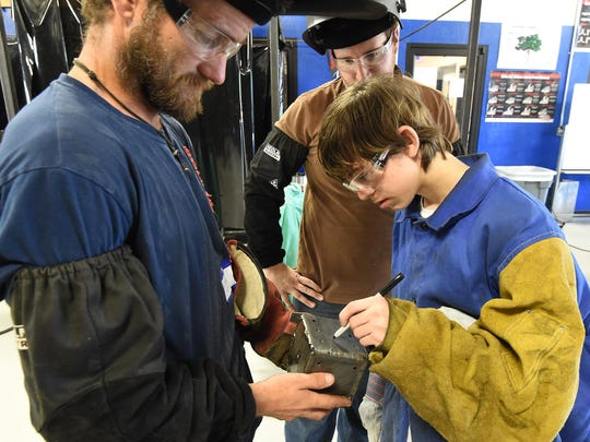 Elliot Schultz, 15, of Bull Shoals, signs a die he welded on Tuesday while welding students Jason Brown, right, of Three Brothers, and Hunter Stevens, of Mountain Home, watch.
