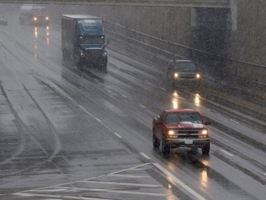 Automobiles travel south along Interstate 75 Tuesday morning as snow falls at the Lockland split.