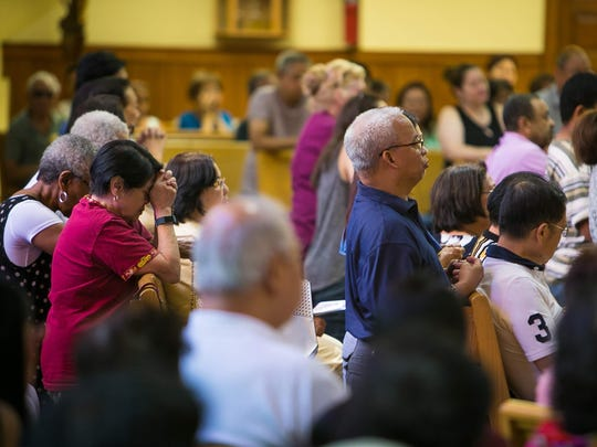 Parishioners attend a nine-day novena (prayer) ceremony to remember the Trinidad family. Audie Trinidad, who was an usher at Saint Anastasia Catholic Church, always saved a spot for his family during Sunday services.