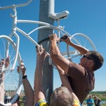 Bryce Reeves locks a ghost bike to a pole on Kechter Road above Interstate 25, the site where 59-year-old cyclist Steve Studt was critically injured June 26 in an accident with a dump truck. Studt died of his injuries. Members of the cycling community placed a ghost bike in his memory and to alert drivers to the presence of cyclists on area roads.