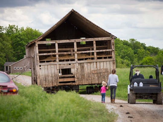 Larry Cleverley, right, and family friend Caitlin Cunningham with daughter Ruby, 3, follow his 1870's barn moves along a farm lane toward his home near Mingo Tuesday, May 23, 2017. Cleverly's fight with DOT to not take portions of his organic farm for Highway 330 restructuring was not in his favor.  He did convince the DOT to pay for the move of his barn to another location on his property.