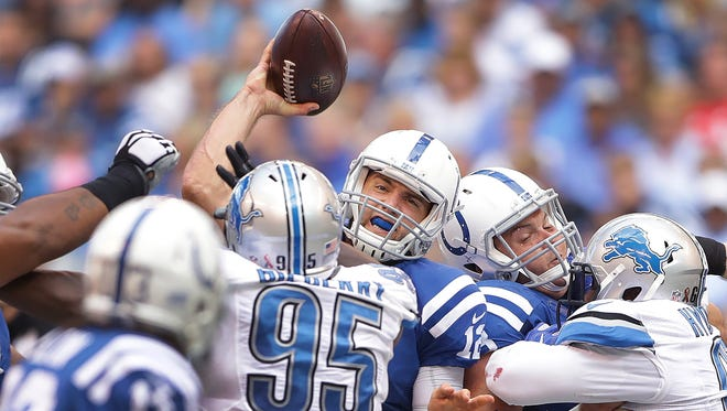 Indianapolis Colts quarterback Andrew Luck (12) attempts to get a pass away under the pressure of the Detroit Lions defense in the first half of their game Sunday, September 11, 2016, afternoon at Lucas Oil Stadium.