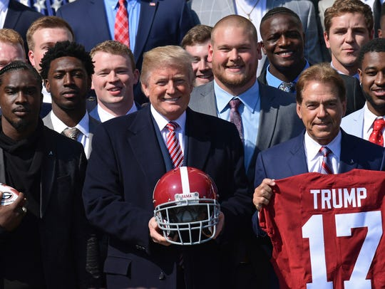 President Donald Trump, center, poses for a photo with the 2017 national champion Alabama football team and coach Nick Saban, right, in April.