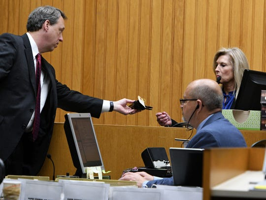 Prosecutor Stephen Crump hands a holster in evidence to the first witness Cindy Wilkerson Tuesday, May. 2, 2017 during the trial of Raynella Dossett Leath. Leath  faces an extraordinary third trial this week in Knox County Criminal Court on the same charge for which she was tried twice before — that she killed her second husband.