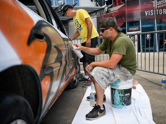 Artist Audie Adams and Ryan Shrader paint the wildly