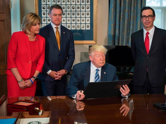 Rep. Claudia Tenney (L), R-NY, and Sen. David Perdue (2nd L), R-Georgia, look on with Treasury Secretary Steven Mnuchin (R) as President Donald Trump (C) looks over the paperwork before signing finical services executive orders and memorandums at the US Treasury Department in Washington, DC, April 21, 2017.