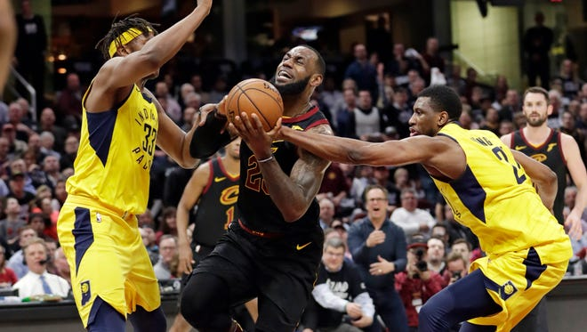 Cleveland Cavaliers' LeBron James, center, drives between Indiana Pacers' Myles Turner, left, and Thaddeus Young during the first half of Game 2 of an NBA basketball first-round playoff series Wednesday, April 18, 2018, in Cleveland.