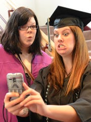 Lauren Krause, left, and Katie Meulemans ham it up for a picture during the University of Wisconsin-Green Bay mid-year commencement ceremony at the Weidner Center on Saturday.