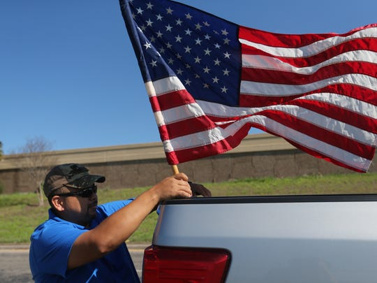 Julio Ferrufino hangs a flag on his truck while he waits for President Trump to pass by Tuesday, Aug. 29, 2017, near Corpus Christi International Airport.
