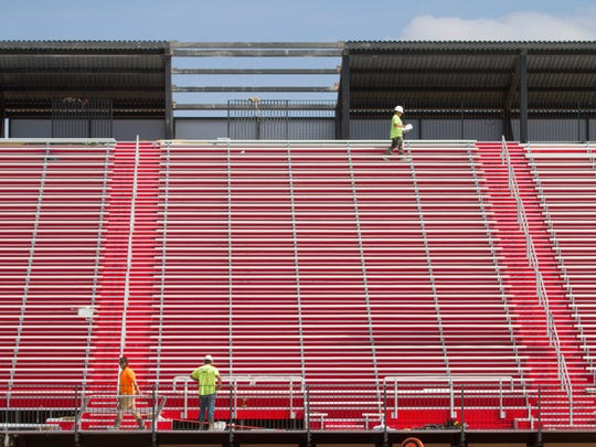 Crews install the expansion of the Dixie State University football stadium Saturday, April 7, 2018.