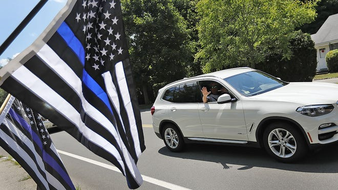 Supporters hold the thin blue line flags on July 28 in front of Hingham Police Station.