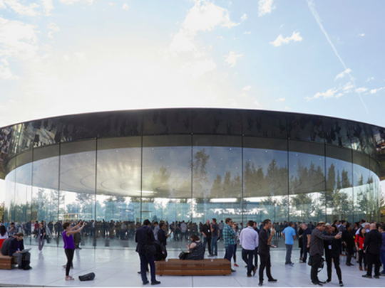 Apple's Steve Jobs Theater is shown with its rounded glass outer wall and a blue sky background