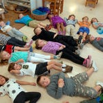 Students lay on the floor while doing a deep breathing exercise during a morning meditation led by kindergarten teacher, Laura Patterson, not pictured, at Highland Presbyterian Church Nursery and Weekday School.    October 23, 2015