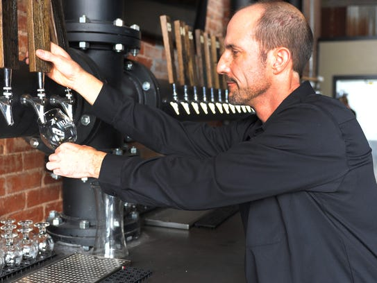 Half Pint Taproom & Restoration Hall owner Dent Keltner tests one of several beer taps the business will feature after the Monday evening grand opening.
