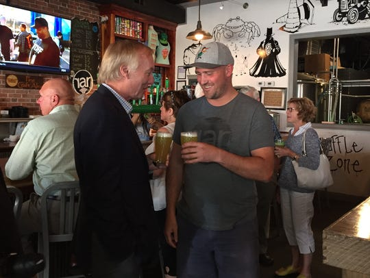 Maryland Comptroller Peter Franchot, left, clinks glasses