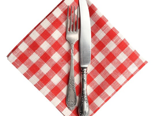 Knife and fork on red plaid napkin isolated.