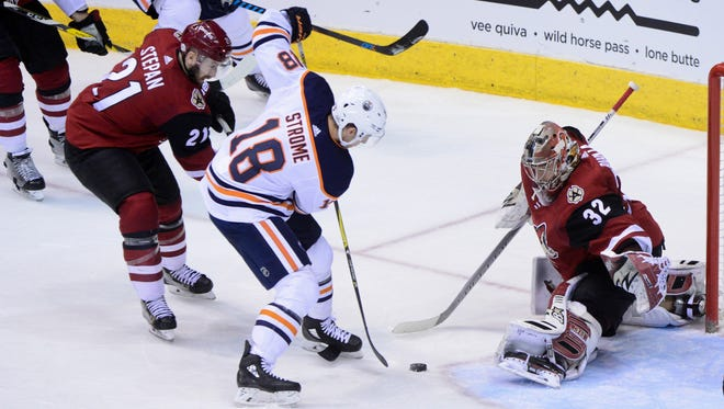 Feb 17, 2018: Edmonton Oilers center Ryan Strome (18) tries to shoot as Arizona Coyotes center Derek Stepan (21) and goalie Antti Raanta (32) defend during the second period at Gila River Arena.