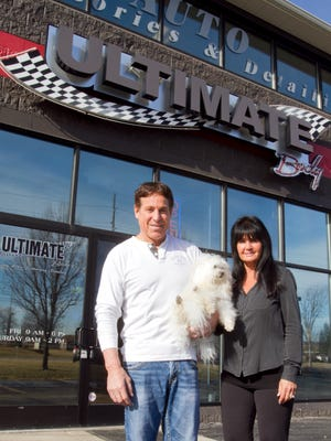 Paul and Donna Almashy, co-owners of Ultimate Body in Brighton, hold their dog Romeo, who stays with them at the newly restored customizing and detailing shop which burned several years ago.