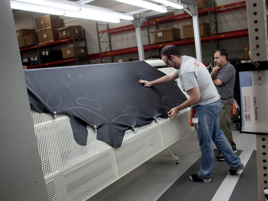 Employees work on a large piece of leather before it is cut for trim components Wednesday, November 11, 2015 at Eissmann Group Automotive, 2440 20th Street in Port Huron. Eissmann will be undergoing a two-phase expansion project, bringing the facility from 60,000-square-feet to 148,000-square-feet by 2018. The project is expected to increase employment from 108 to 160 jobs in 2016, with the possibility of more than 300 by 2018.