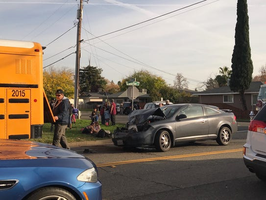 Students hang out on a lawn behind this damaged car.