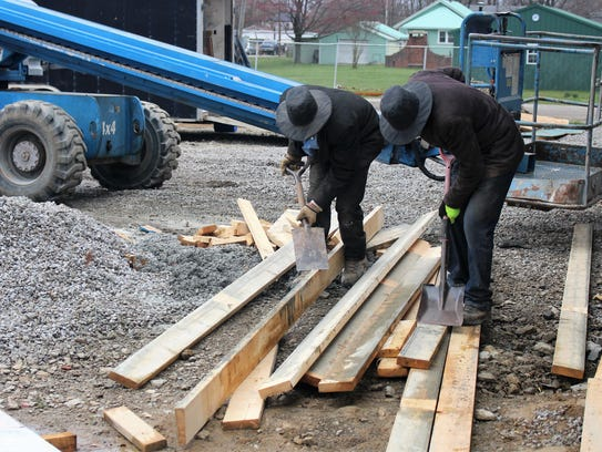 Two workers scrape dirt off pieces of wood as construction is underway for the new swine barn.