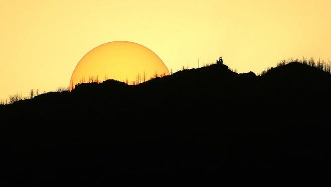 A setting sun silhouettes Monjeau fire lookout tower, at right, in the Lincoln National Forest near Ruidoso.