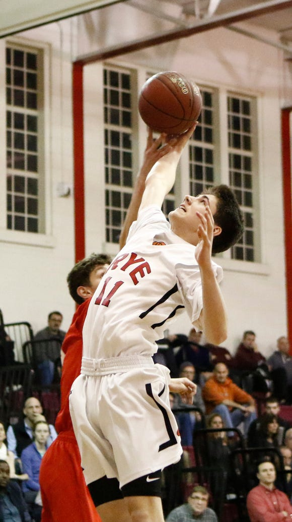 Rye's Quinn Kelly (11) reaches for a rebound during