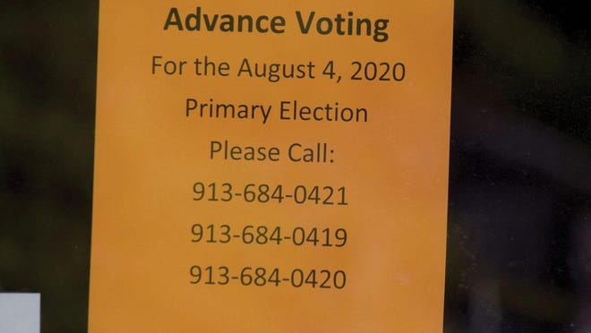 This sign is posted at an entrance at the Leavenworth County Courthouse. People can call the phone numbers in order to gain entry to the courthouse to vote in advance for the primary election.