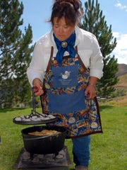 Terry Bell has been cooking with Dutch ovens for more than 30 years. As the Dutch Diva, she teaches classes, cooks for events and outings, and competes in Dutch oven contests. Here, she checks on Parmesan rolls at her Verdi ranch.