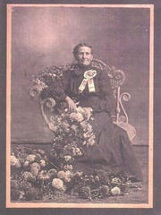 Florence Wolf was a champion gardener who won many ribbons at county and state fairs. Here she is looking like royalty in an elegant wicker chair with a first-place ribbon pinned on her dark dress and flowers draped across her lap and feet.