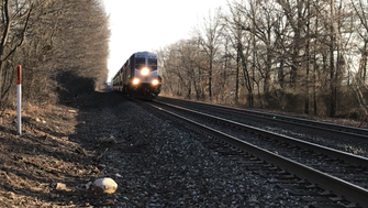 A Bergen line NJ Transit train roars through a Glen Rock woods parallel to Nottingham Road.