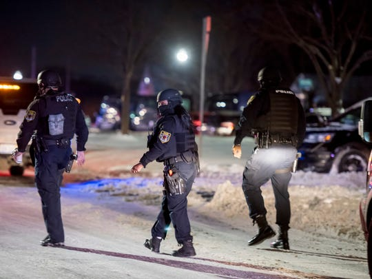 Police officers respond to a scene on East Outer Drive in Detroit.