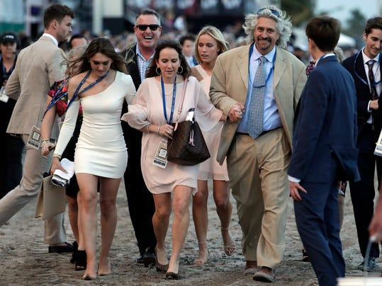 Trainer Steve Asmussen, third from right, walks to the winner's circle after Gun Runner won the Pegasus World Cup Invitational horse race, Saturday, Jan. 27, 2018, at Gulfstream Park in Hallandale Beach, Fla. (AP Photo/Lynne Sladky)