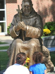 People pray at the statue of St. Padre Pio during the St. Padre Pio Festival in Vineland, New Jersey om September 2014. USA Today Network