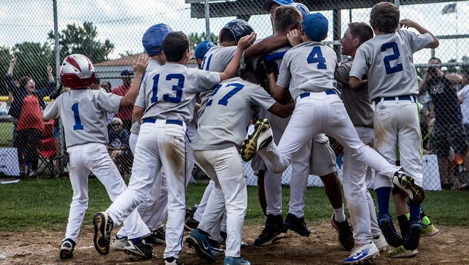 Licking Memorial Hospital teammates mob Trey Robinson, after his home run capped a rally in the Licking County Shrine Tournament Varsity semifinals at Mound City.