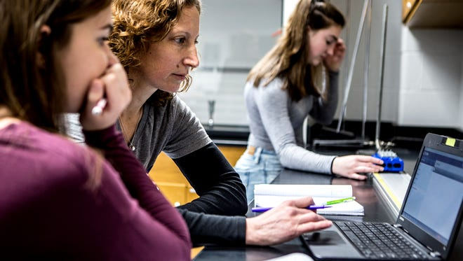 Diane McDonald, a math and physics teacher at Granville High School, works with students during an in class lab.