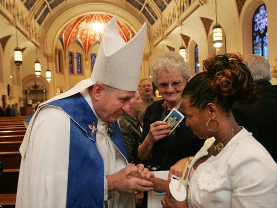 On the eve of his installation, Bishop Richard Pates visits with Christine Muriu of Des Moines after an evening prayer service at St. Ambrose Cathedral in 2008.