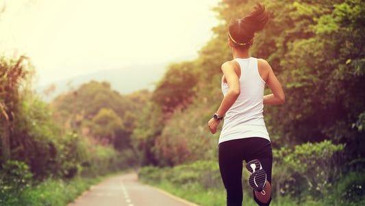 A woman runs on a trail