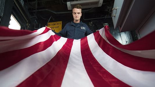 Navy Petty Officer 3rd Class Scott Farrell folds the American flag aboard the guided-missile cruiser Chancellorsville in the South China Sea on July 9.