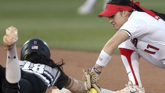 Arizona shortstop Mo Mercado (11) just gets down the tag on New Mexico State's Rachel Rodriguez (18) during the third inning of an NCAA softball tournament regional game Friday night in Tucson, Ariz.