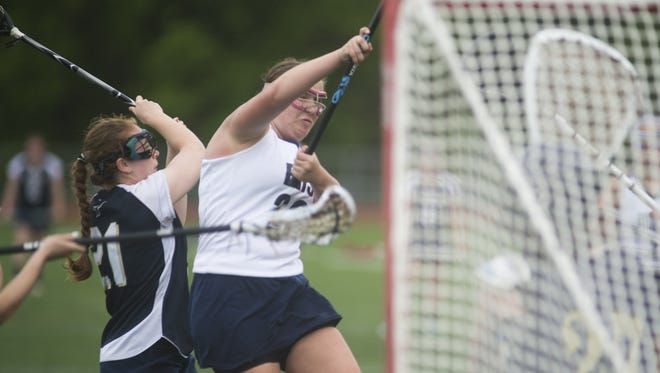 Burlington's Monica Weltman, center, forces a hole in the Essex defense to fire a shot on goal during girl's lacrosse at Burlington on Friday.