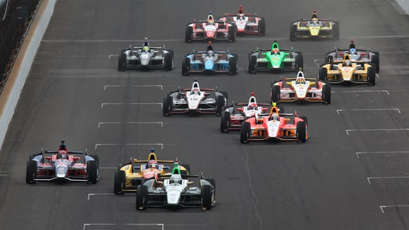 Pole sitter Ed Carpenter leads the field at the start of the 97th running of the Indianapolis 500 at Indianapolis Motor Speedway on May 26, 2013. Behind him are front row starters Carlos Munoz (center) and Marco Andretti (left).