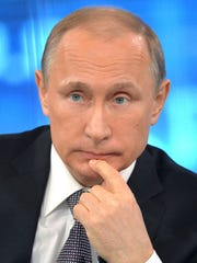 Russian President Vladimir Putin listens to a question