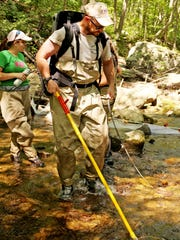Staunton resident Pat Harmon wears an electrofishing backpack as he shocks fish in Paine Run in Augusta County for stream sampling research for his master's degree he is earning through JMU.
