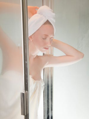 Young woman exiting a steam shower.