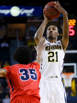 Michigan Wolverines guard/forward Zak Irvin (21) shoots over Detroit Titans guard Paris Bass (35) in the first half at Crisler Center.