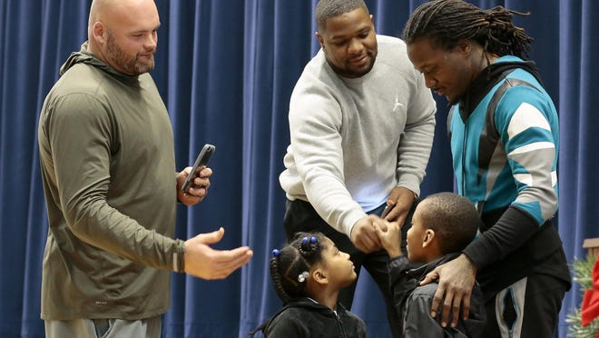 Bengals players Andrew Whitworth, Vontaze Burfict and Adam Jones shake hands with student Larenzo Floyd after he reads his essay at Lincoln Heights Elementary School on Tuesday. After the students were called to an assembly where they thought just three bikes would be given away as prizes in an essay contest, the Bengals teammates surprised the children with bikes for everyone.