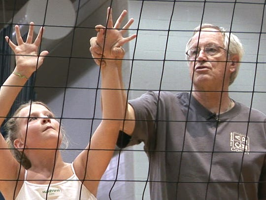 Bruce Koller, right, coached the Central York boys' volleyball program to four state titles along with his wife, Barb, in the 1970s and 1980s. Here, he shows camper Madysen Mann how to hold her hands to block a shot at the net in this 2009 photo.