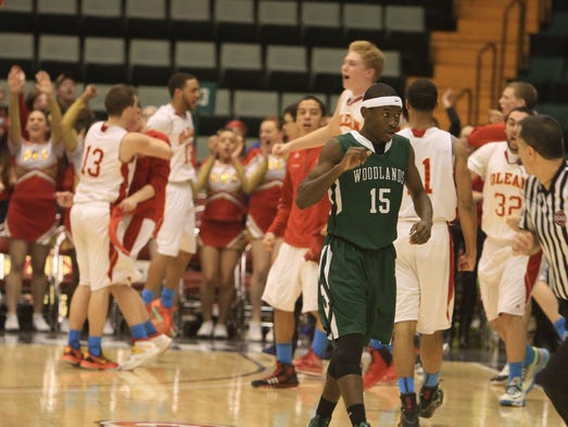 Woodlands' Ross Joseph (15) walks off the court as Olean players celebrate their 71-63 victory in the boys Class B semifinal state championship basketball game at the Glens Falls Civic Center March 14, 2014.