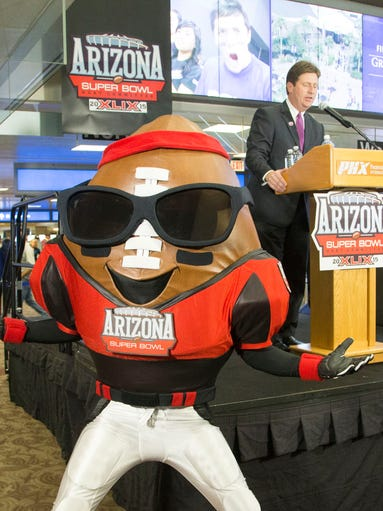 Phoenix Mayor Greg Stanton speaks while mascot Spike